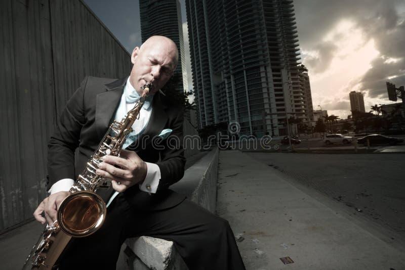 Mann in einem Smoking, der ein Saxophon spielt lizenzfreies stockfoto