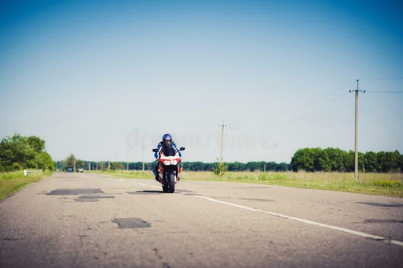 Mann in einem Sturzhelm fährt entlang die Straße auf ein Motorrad lizenzfreie stockfotos