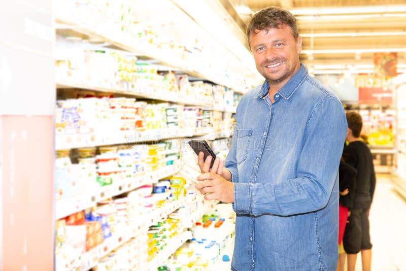 Mann in einem Supermarktgeschäftstest die Produkte mit seinem Telefonanwendung Smartphone App stockbild