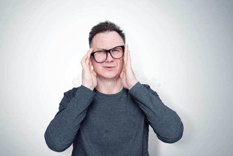 Mann in einem T-Shirt und in den Gläsern hält seinen Kopf in seinen Händen Kopfschmerzen lizenzfreie stockfotografie