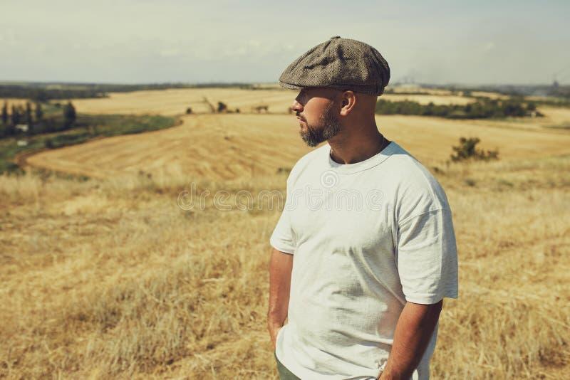 Mann in einem T-Shirt und in einer Kappe auf dem Hintergrund von Getreidefeldern lizenzfreies stockfoto