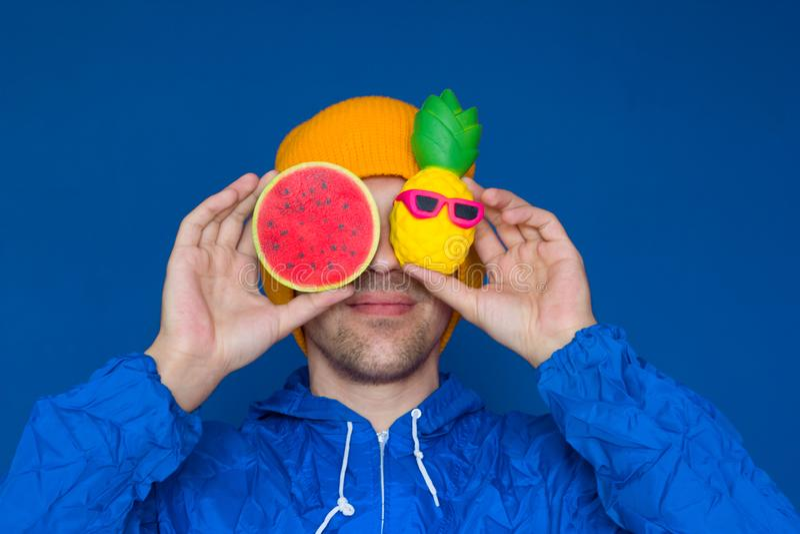 Mann in einer blauen Artjacke des Sports 90s und in einem gelben Hut mit squishy Wassermelonen- und Ananasspielwaren stockbild