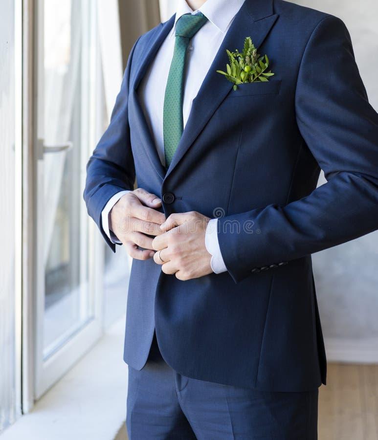 Mann in einer blauen Klage mit einem Boutonniere vor dem Fenster, der Bräutigam stockbild