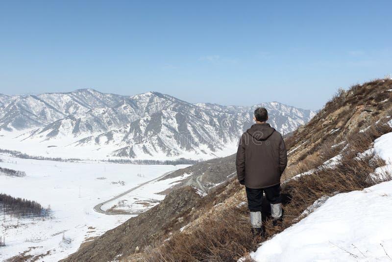 Mann in einer braunen Jacke, die von einer Höhe zu den Bergen schaut stockfotos