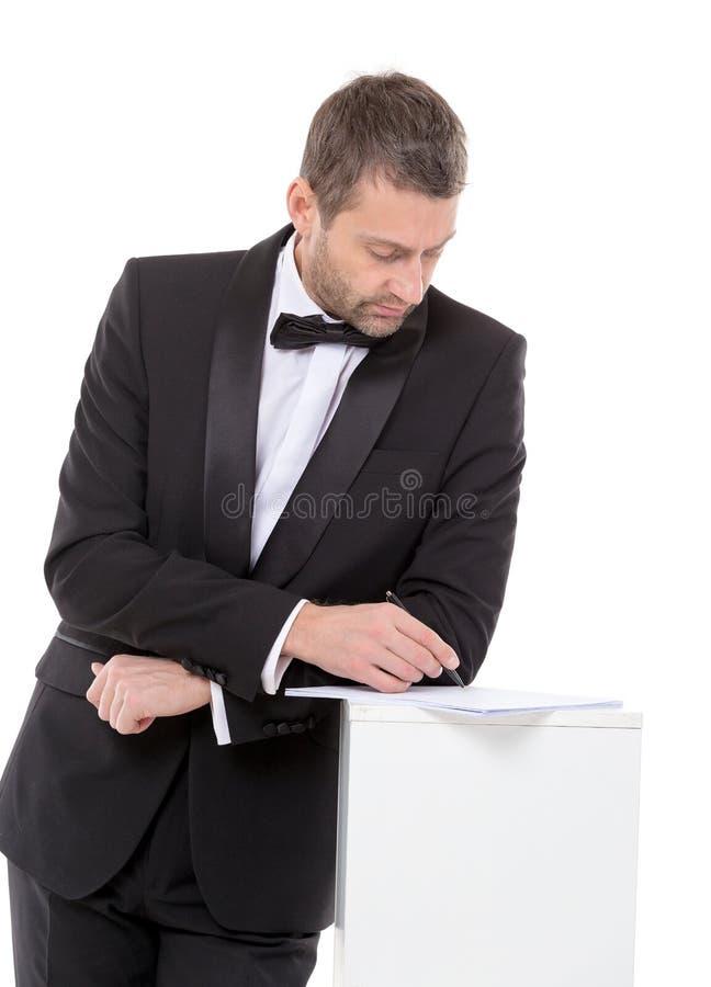 Mann in einer Fliege, die ein Formular ausfüllt stockbild