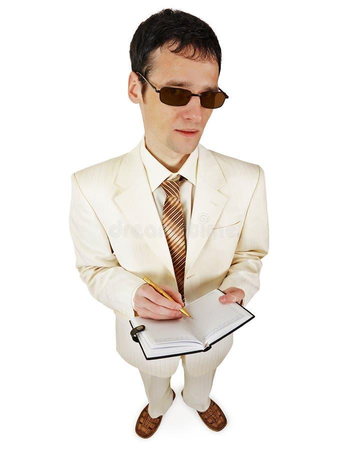 Mann in einer hellen Klage mit einem Notizbuch auf weißem Hintergrund stockfotografie