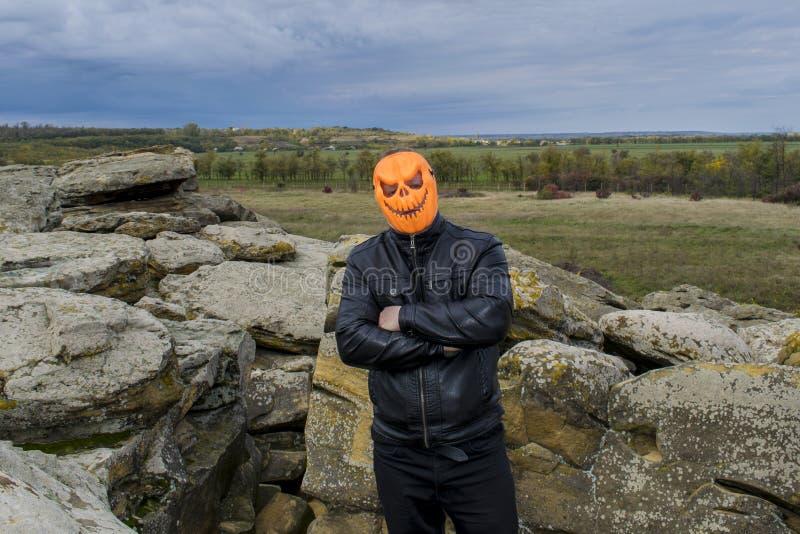 Mann in einer Kürbismaske in den Bergen lizenzfreie stockfotos