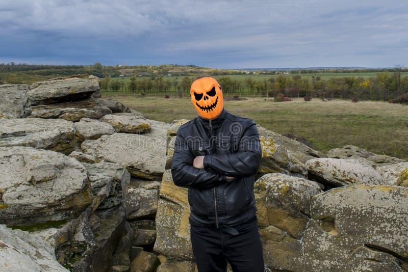 Mann in einer Kürbismaske in den Bergen stockbilder
