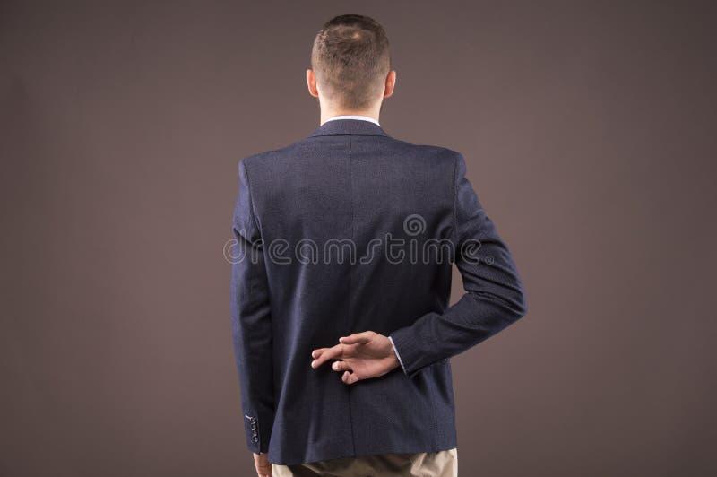 Mann in einer Klage kreuzte seine Finger hinter seinem zurück lizenzfreies stockfoto