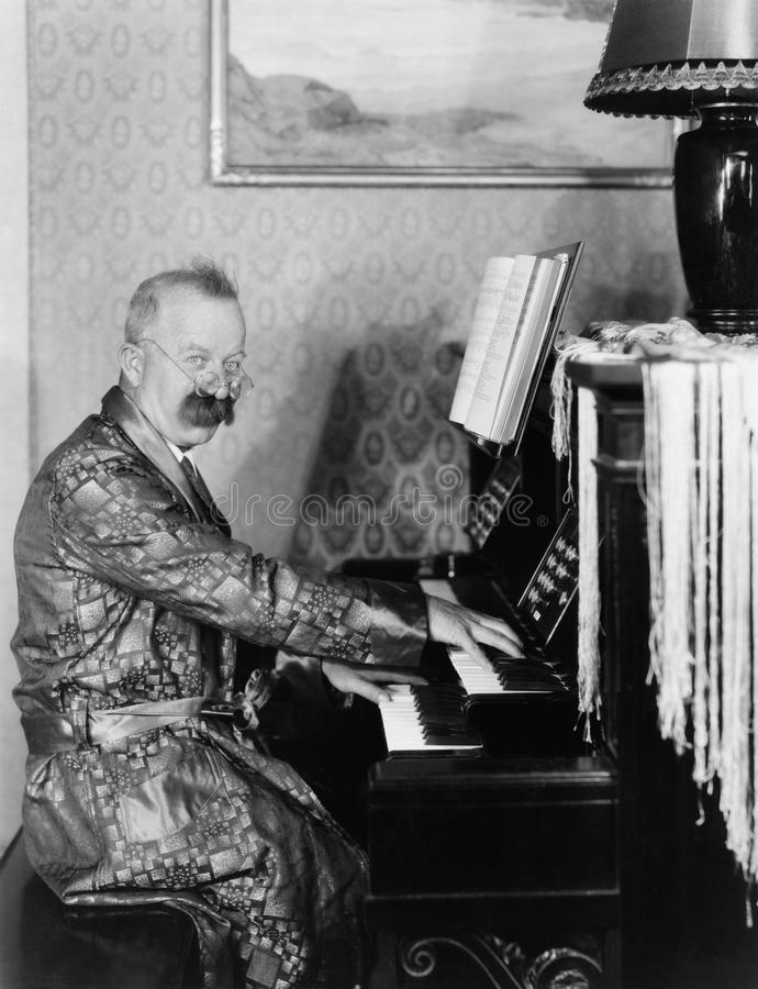Mann in einer Robe, die sein Klavier im Wohnzimmer spielt (alle dargestellten Personen sind nicht längeres lebendes und kein Zust lizenzfreie stockbilder