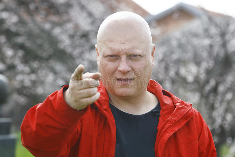 Mann in einer roten Jacke, die mit dem Finger und den Alarmen droht stockbilder