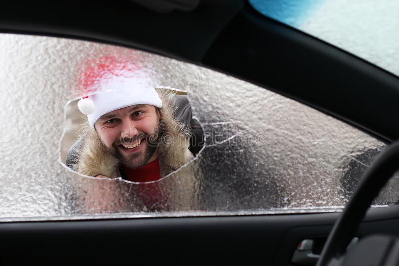 Mann in einer roten Kappe von Santa Claus in einem Auto mit defektem Glas stockfotografie