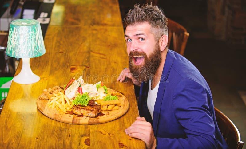 Mann empfing Mahlzeit mit gebratenen Kartoffelfischen haftet Fleisch und lavash Genie?en Sie Mahlzeit Er verdient k?stliche Mahlz lizenzfreie stockfotografie