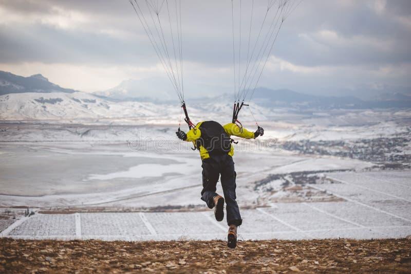 Mann entfernt sich mit dem speedglider vom Berg stockfotos