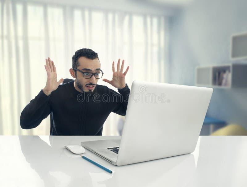 Mann entsetzt, Mitteilung auf Computer im Büro lesend stockfotos