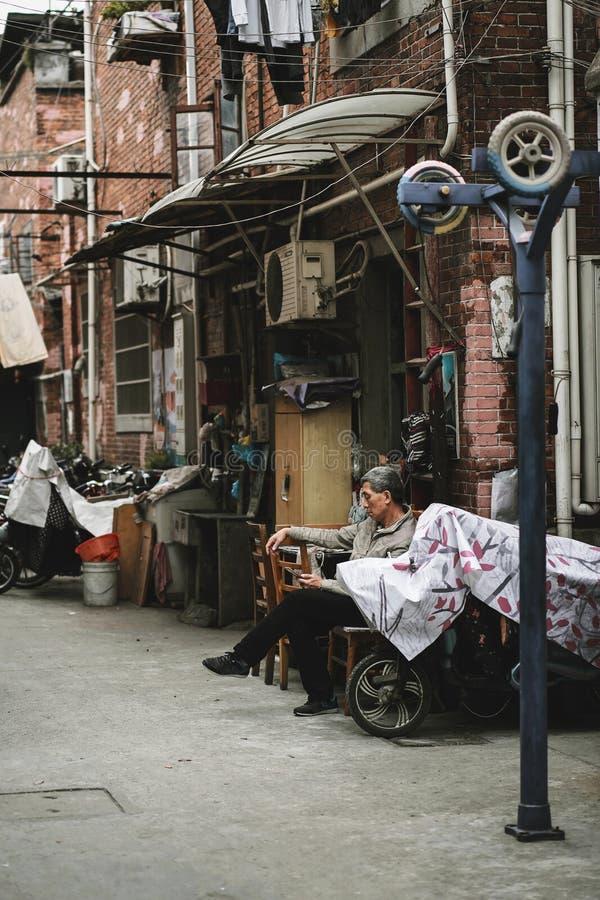 Mann entspannt sich vor seinem Haus in Hongkou-Bezirk lizenzfreies stockbild