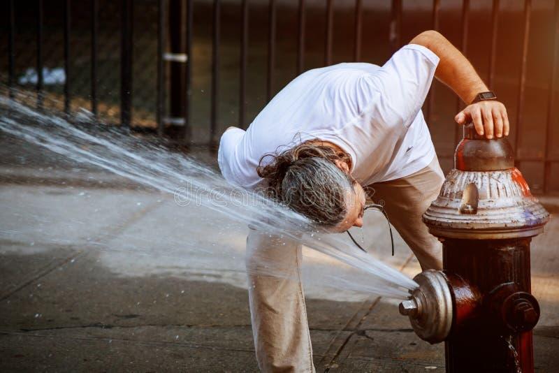 Mann erneuert sich öffentlich quadratische Sommerhohe temperatur mit Hydrantwasser stockfotografie