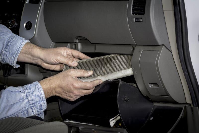 Mann ersetzt den Filter, der nahe Handschuhschachtel gelegen ist stockfotografie