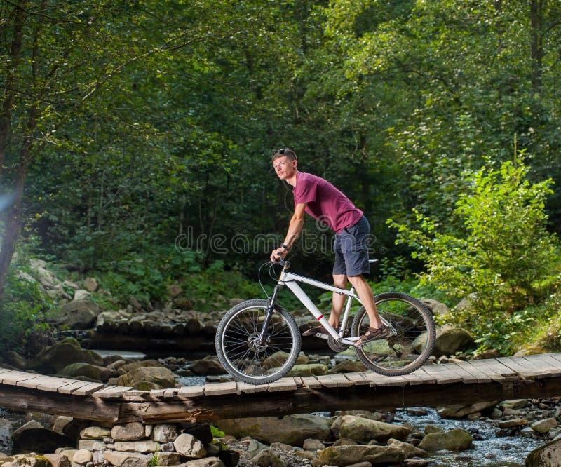Mann fährt Fahrrad durch Holzbrücke über einem Fluss lizenzfreies stockbild