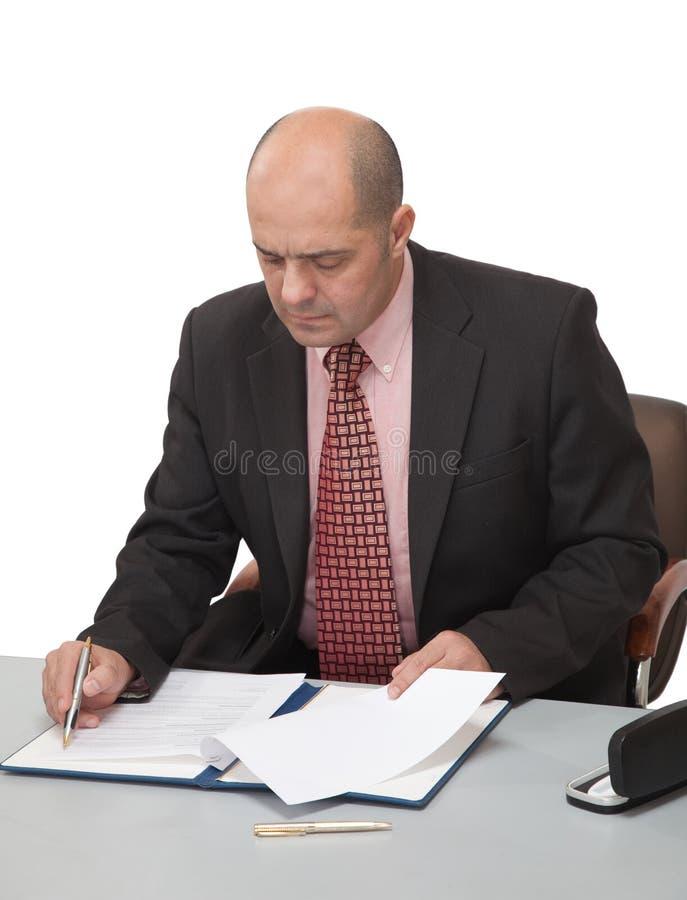 Mann füllt die Papiere und sitzt am Tisch lizenzfreie stockfotografie
