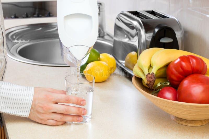 Mann füllt Glas mit Trinkwasser stockbilder