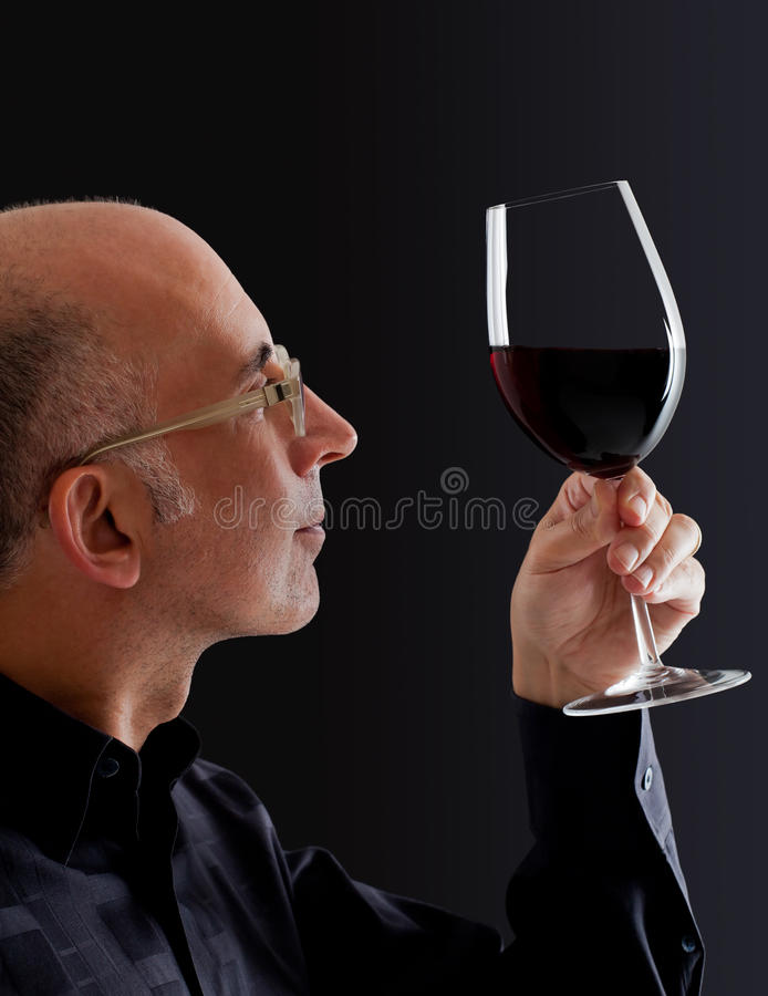 Mann, Farbe im Wein beobachtend stockbilder