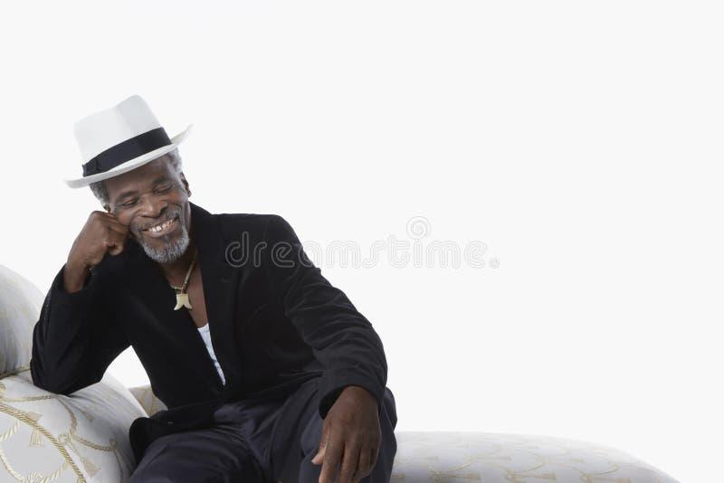 Mann in Fedora On Chaise Lounge stockfotos