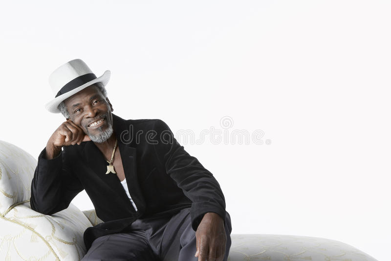 Mann in Fedora On Chaise Lounge lizenzfreie stockfotografie