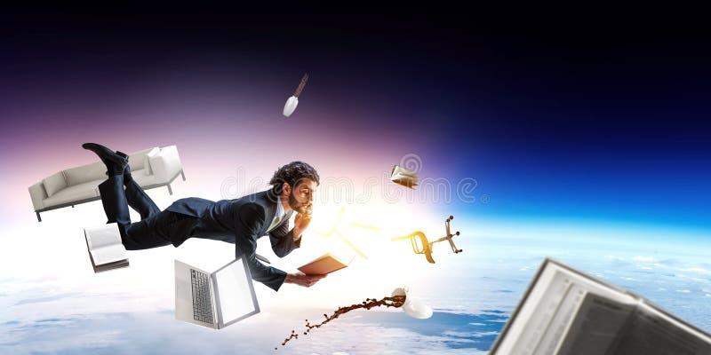 Mann fliegt und arbeitet an Laptop Gemischte Medien stockbild