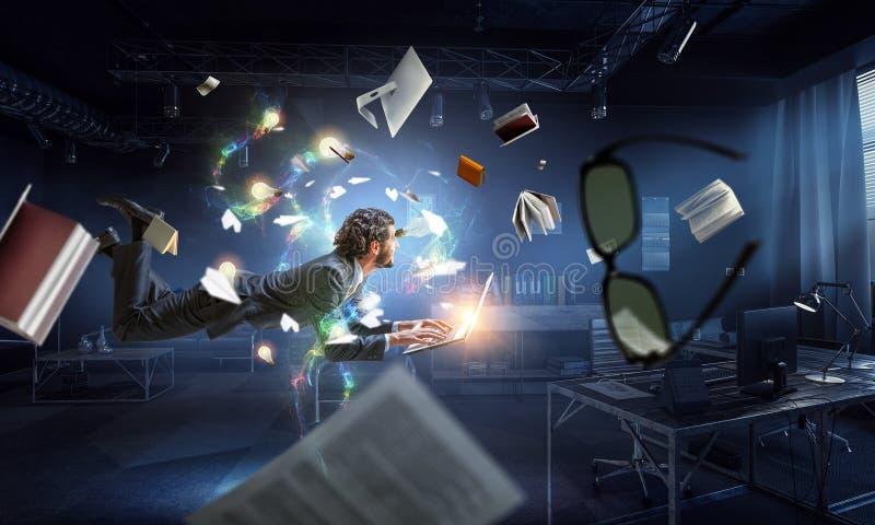 Mann fliegt und arbeitet an Laptop Gemischte Medien stockfotografie