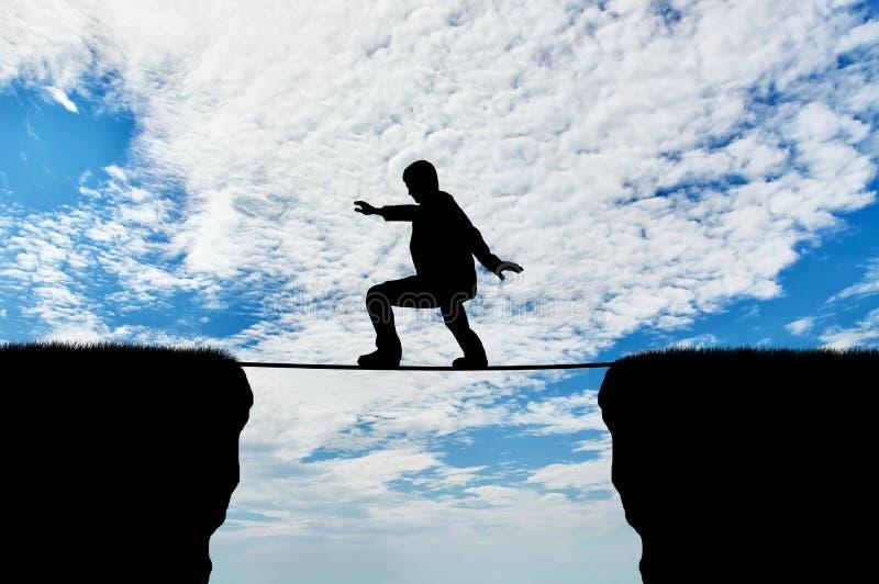 Mann geht auf ein Drahtseil über einer Klippe lizenzfreie stockfotografie