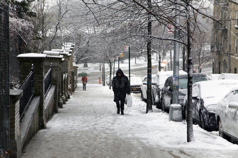 Mann geht herauf Hügel während des Schneefalles in den Bronx New York lizenzfreies stockfoto