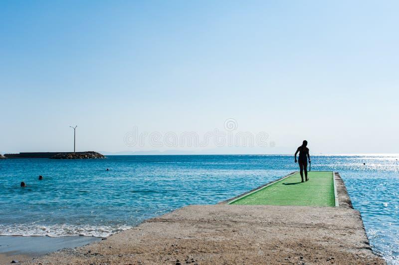 Mann geht zum grünen Pier zu tauchen stockfotos