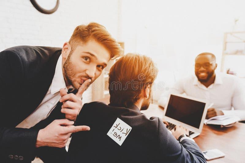 Mann geklebter Aufkleber auf Rückseite des Kollegen im Büro stockfotografie