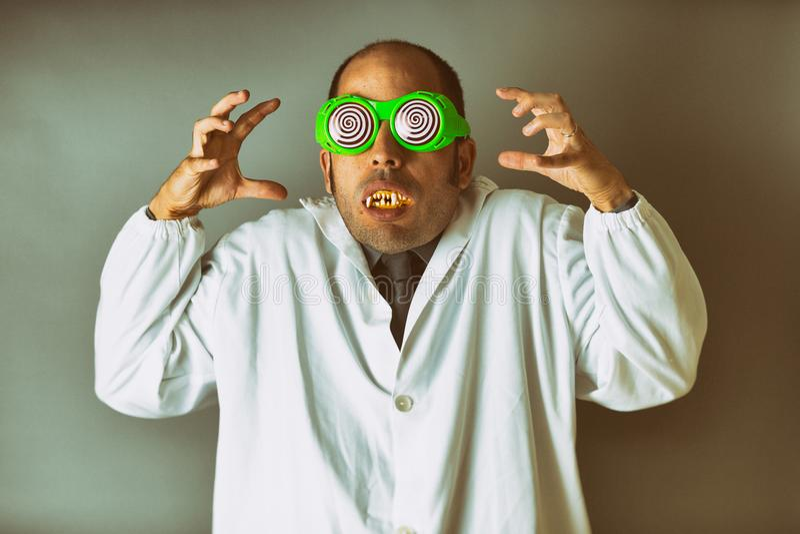 Mann gekleidet als verrückter Wissenschaftler mit einem Laborkittel, verrückten Gläsern und Vampirszähnen stockbild