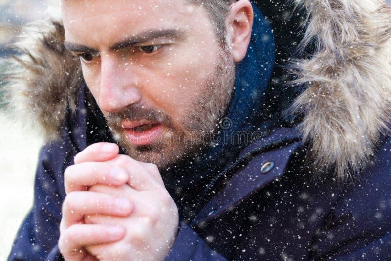Mann gekleidet in der warmen Kleidung im Schneewetter stockfotografie