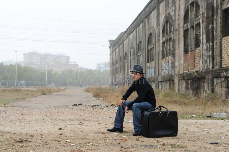 Mann gekleidet im Schwarzen mit dem sitzenden Rauchen des Hutes lizenzfreies stockfoto