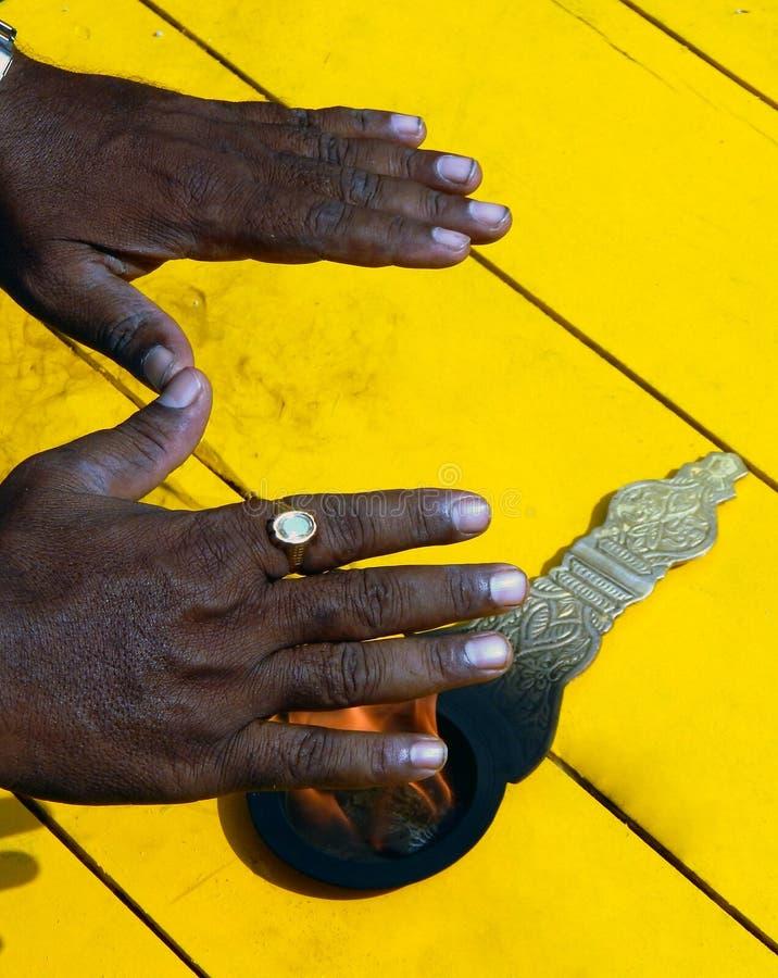 Mann gelangen Segen, indem er Hände an Flammen von Aarti, hindisches religiöses Ritual der Anbetung verwendet stockfotografie