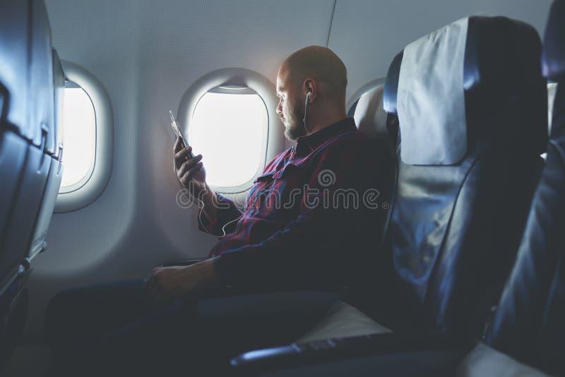 Mann genießt seine Lieblingsmusik über Zelltelefon, während in ein Flugzeug fliegt stockfotografie
