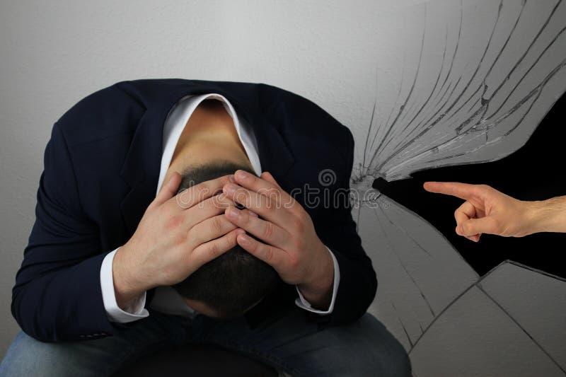 Mann, Geschäftsmann, sitzend, biegen seinen Kopf mit zwei Händen, neben einem Mann gibt die Schuld, zeigen ausdrucksvoll mit eine stockfoto