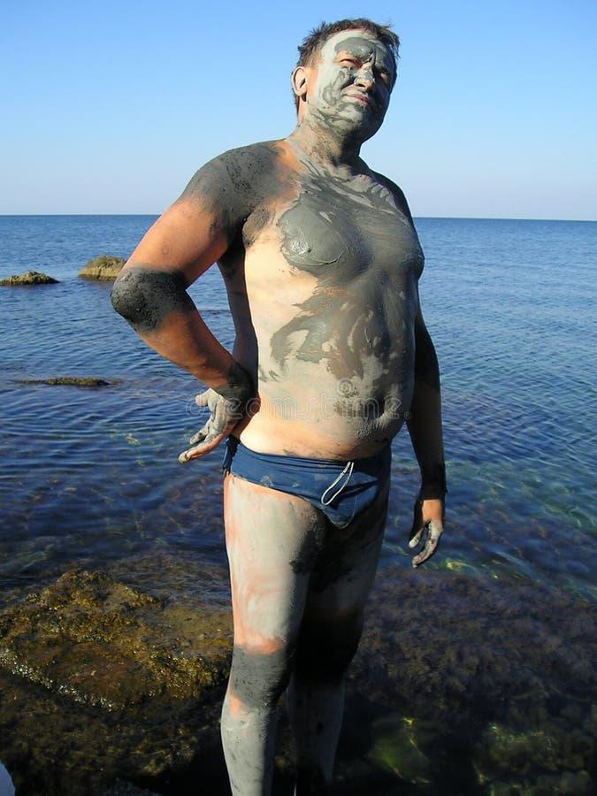 Mann, geschmiert durch Schlamm in Meer lizenzfreies stockbild