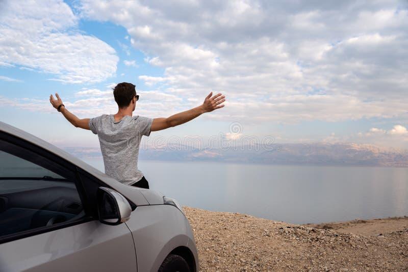 Mann gesetzt auf der Maschinenhaube eines gemieteten Autos auf einer Autoreise in Israel lizenzfreie stockbilder