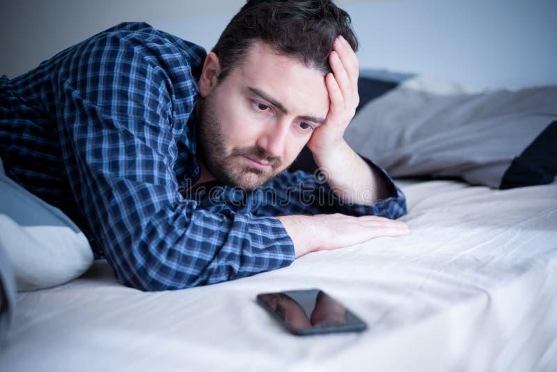 Mann gewöhnt zum Smartphoneporträt im Bett stockfotos