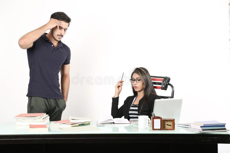 Mann gibt Ausdruck und Frau sitzt stockfotografie