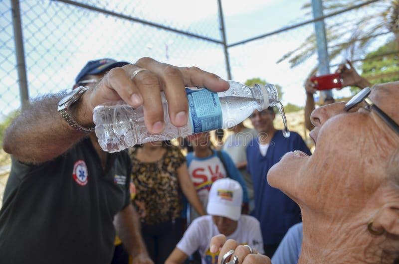 Mann gibt einer alten Dame Wasser stockfoto