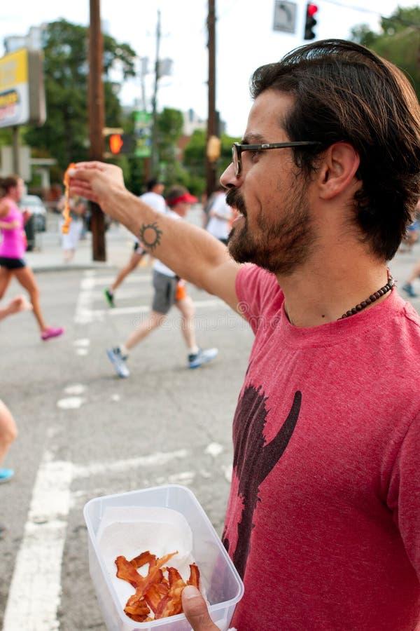 Mann gibt heraus Speckstreifen zu den Läufern in Atlanta-Rennen stockbilder