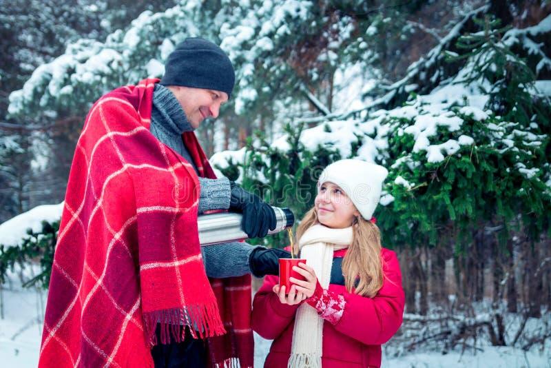 Mann gießt heißen Tee aus Thermosflasche für seine Tochter heraus stockfoto