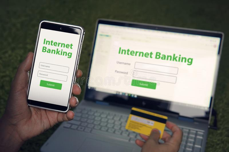 Mann graste homepage des Onlinebankingservices an seiner Smartphone- und Laptopholdingkreditkarte Online-Zahlungs-Mobile stockbild