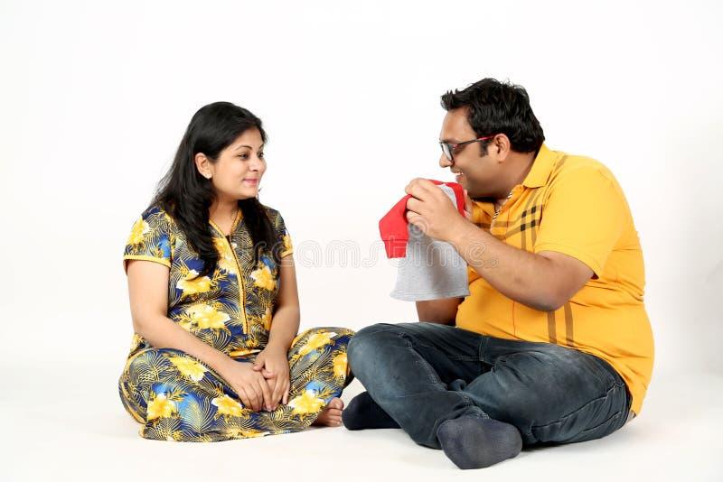Mann hält Babystoff und schwangere Frau schaut Babystoff mit Lächelngesicht lizenzfreie stockbilder