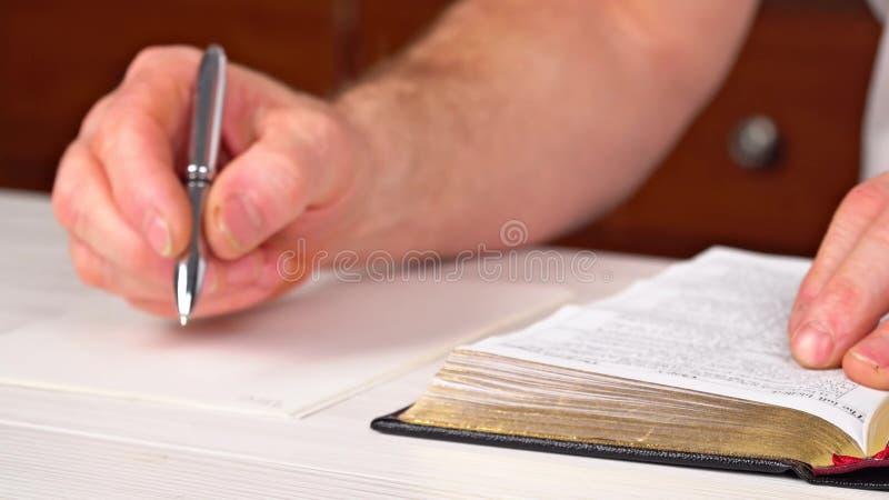 Mann hält einen Stift in seiner Hand mit einem offenen Buch, das vor ihm liegt lizenzfreie stockfotos